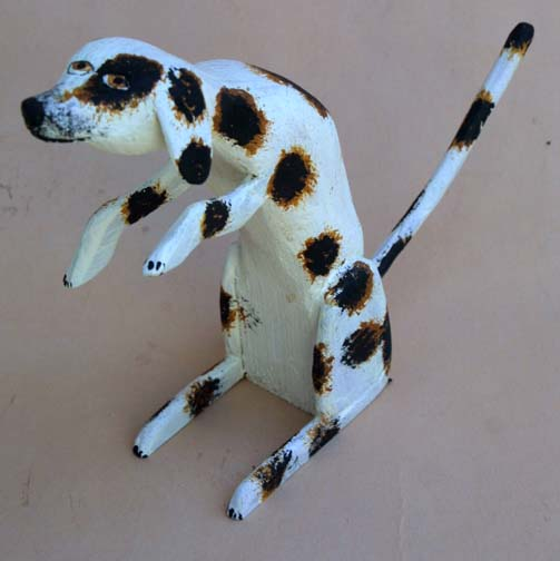 """Spotted Sitting Puppy""   (left paw up)  by Roy MInshew  painted and carved wood  painted carved wood   7"" x 2"" x 9.5"" $225   #8411"