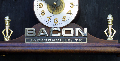 """Porcus Fugit"" Clock by Jason Burnett wood, found objects, prize hog trophy figure, car dealer emblem, trophy torches, Chinese coin/token and other objects 9.25"" x 12"" x 4.5"" $600 #11880"