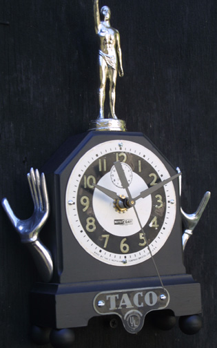 """Taco Time"" clock by Jason Burnett od, found objects: salvaged wooden alarm clock body, modified trophy figure, place card holders, taco manufacturing tag 11.5"" x 6.75"" x 2.5"" $600 #11881"
