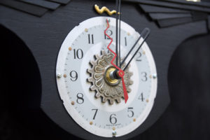 """detail  """"Blame Game""""  Wall Clock by Jason Burnett  wood, found objects: trophy parts, emblem parts, repurposed clock parts  14"""" x 13"""" x 3""""  $350  #12090"""