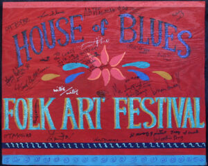 "House of Blues Folk Festival sign 1999 with folk artist signatures paint, glitter on wood with marker signatures 19"" x 23.5"" x .5"" $500 #12845"